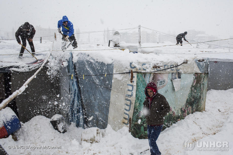 Syrian refugees remove snow from their shelter rooftops at an informal tented settlement in the Bekaa Valley, Lebanon, on 7 January 2015. ; Winter storm Zina swept through the region blanketing higher ground with snow and bringing harsh conditions to millions of refugees.